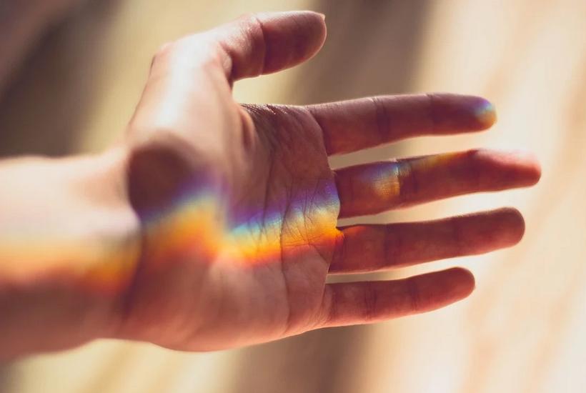 Hand mit Regenbogenlicht