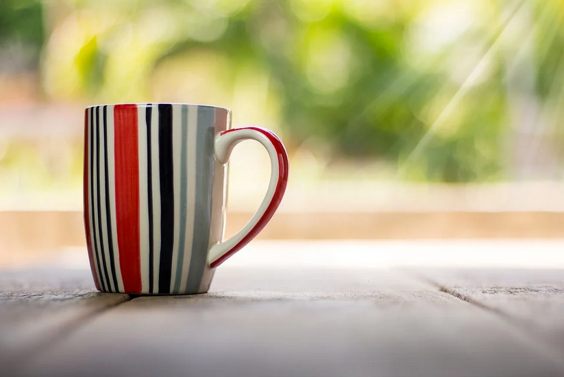 bunte Kaffeetasse steht auf einem Holzbrett