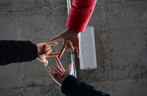 BLICKWINKEL Beispielfoto - Drei Jugendliche halten ihre Hände in der Mitte