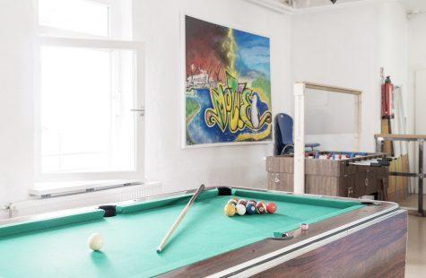 Aufenthaltsraum im Jugendbereich mit Billiardtisch, Tischkicker und Graffitti an der Wand