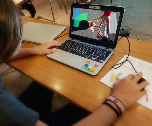 Kind sitzt an Schreibtisch und arbeitet an einem Laptop